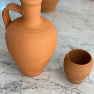 A clay pot + a clay cup , for drinking water